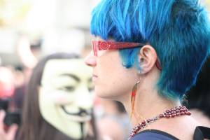 Image of a blue-haired protestor and a Vendetta mask