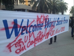 "A banner reading ""Welcome World Social Forum"" over which has been spraypainted ""ACAB"" and ""Forum du Capital"""