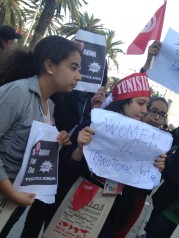 Young women holding signs in support of transitional justice