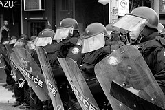 A line of riot police with helmets and shields
